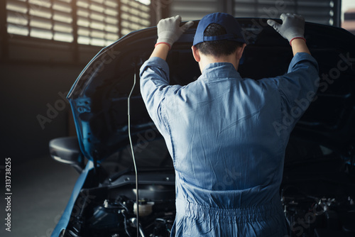 obraz dibond Car mechanic opening car hood for internal checking to maintenance vehicle by customer claim order in auto repair shop garage. Engine repair service. People occupation and job. Automobile technician