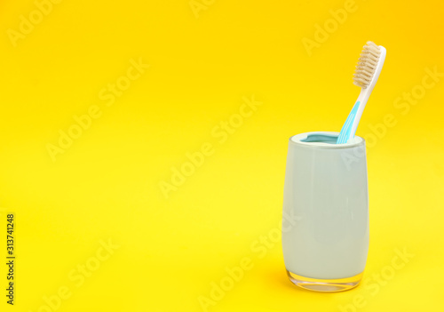 Fotografie, Obraz  Natural bristle toothbrush in holder on yellow background
