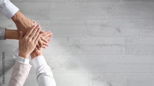 People holding hands together over light wooden background, top view with space for text Slika na platnu