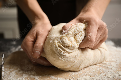 Fototapeta Woman beating dough at table, closeup. Making pasta obraz