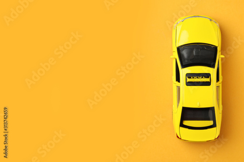 Tableau sur Toile Yellow taxi car model on orange background, top view
