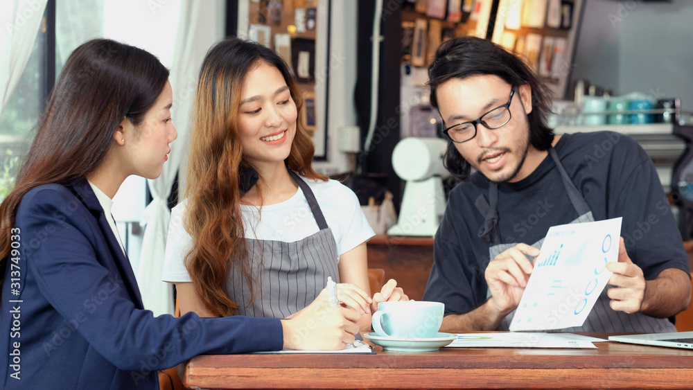 Fototapeta Young asian business woman discussing about financial planning with small business owner at cafe coffee shop, Business meeting corporate partnership, Asia financal loan for start up new business