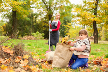 Mother And Daughter Cleaning Up Autumn Leaves Outdoors