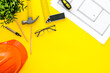 Leinwanddruck Bild - Builder work desk with hard hat, instruments and blueprints on yellow background top-down frame copy space