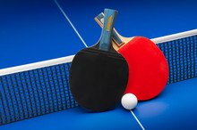 Ping Pong Rackets And Balls On A Blue Table With Net.