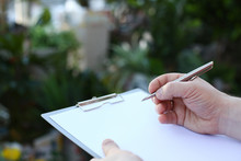 Human Hand Writing On Clipboard With White Paper