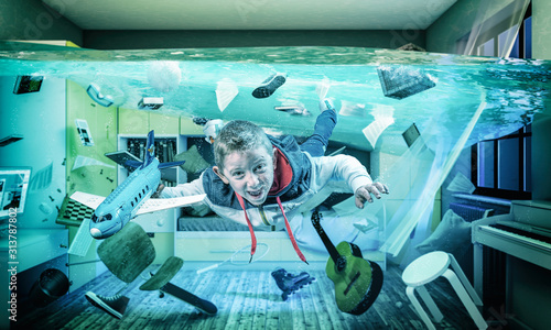child plays happy with an airplane in his flooded room.