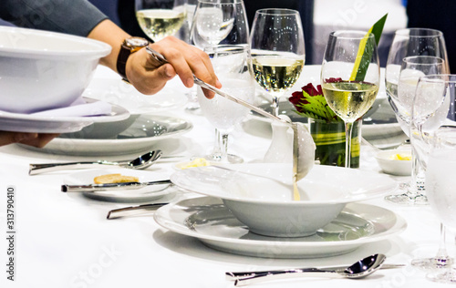 Obraz Table side service at a fine dining restaurant, Waiter serving dishes to the table - fototapety do salonu