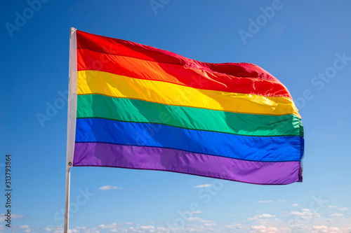 Fototapeta Rainbow gay pride flag against blue sky obraz