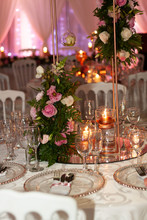Rose Gold Table Decor At A Wedding Reception With Roses