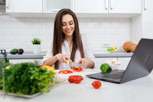 Young cute brunette housewife cooking following the Internet recipes and cutting Canvas Print