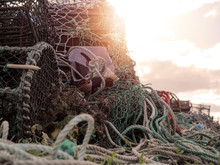 Fish And Crab Traps And Ropes Stacked In Chaotic Order. Cloudy Sky In The Background With Sun Flare. Concept Fishing Equipment, Chaos. Mess,