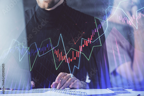 Forex graph with businessman typing on computer in office on background. Concept of analysis. Double exposure.