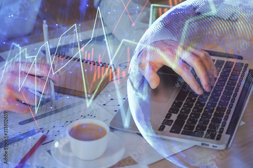 Forex graph with businessman working on computer in office on background. Concept of hardworking. Double exposure.