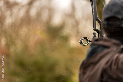 Tablou Canvas Close-up of an archer, back view, while aiming with a hunting compound bow, with