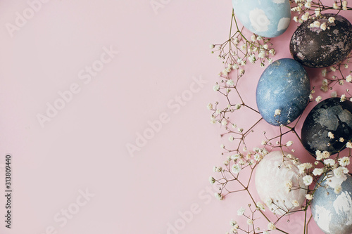 Stylish easter eggs and spring flowers border on pink paper flat lay, space for text Canvas Print