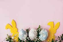 Happy Easter. Stylish Easter Eggs, Yellow Bunny, Spring Flowers On Pink Paper Table Flat Lay, Space For Text. Natural Dyed Easter Eggs And Rabbit Decorations. Card Mockup