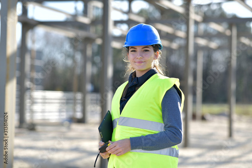 young woman apprentice standing on construction site Wallpaper Mural