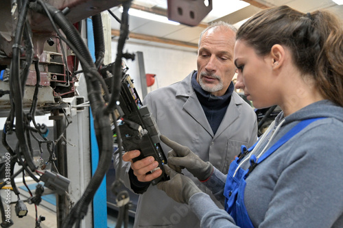 Trainee with mechanics manager working on car technology - 313819069
