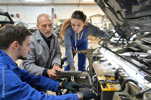 Instructor with trainees working on car engine Fototapeta
