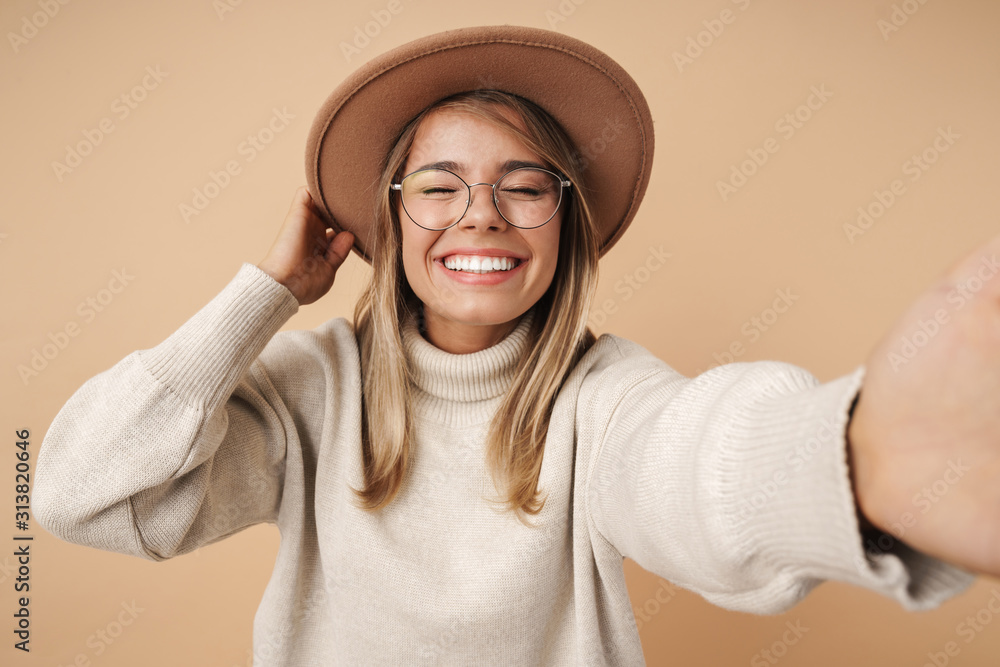 Fototapeta Portrait of cheerful young woman smiling and taking selfie photo