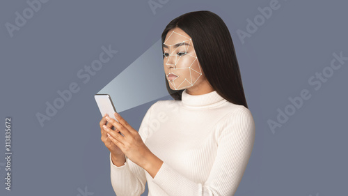Obraz Biometric verification. Girl with smartphone using face ID - fototapety do salonu