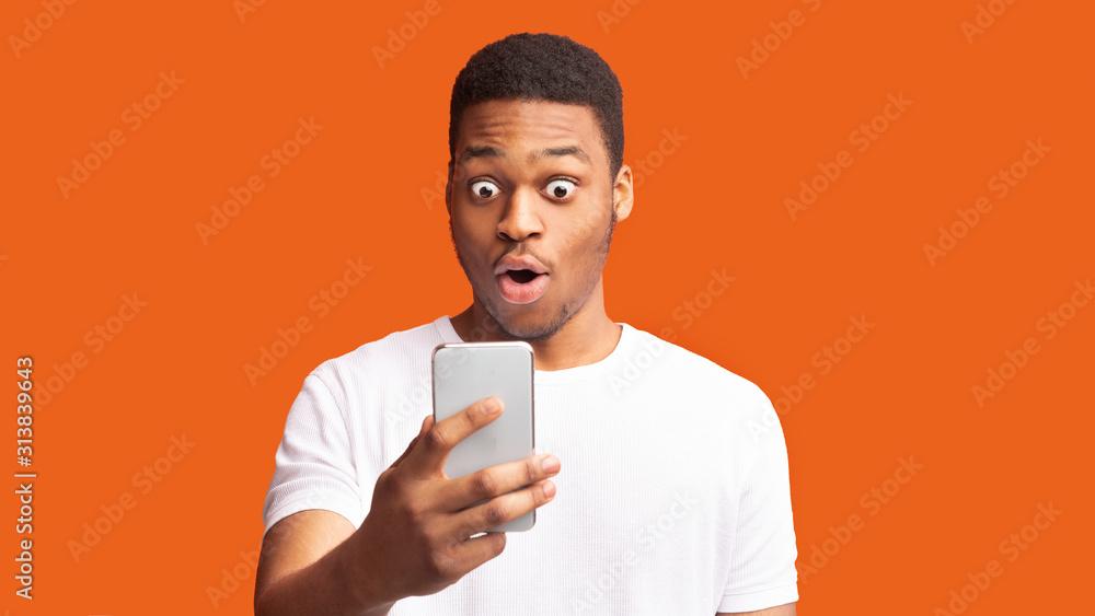 Obraz Closeup portrait of surprised african guy looking at phone fototapeta, plakat