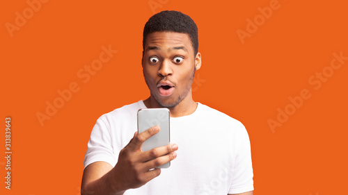 Obraz Closeup portrait of surprised african guy looking at phone - fototapety do salonu