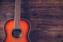Cropped Image Of Vintage Style Travel Size Acoustic Guitar With Rosewood Neck And No Pickguard On Grunged Dark Wood Textured Background. Close Up, Copy Space For Text, Top View.