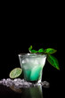 A refreshing beautiful cocktail with ice, lime and mint. On a black background, vertical
