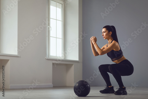 Squat exercises. Girl in black sportswear with dumbbells in her hands doing squats in a room.