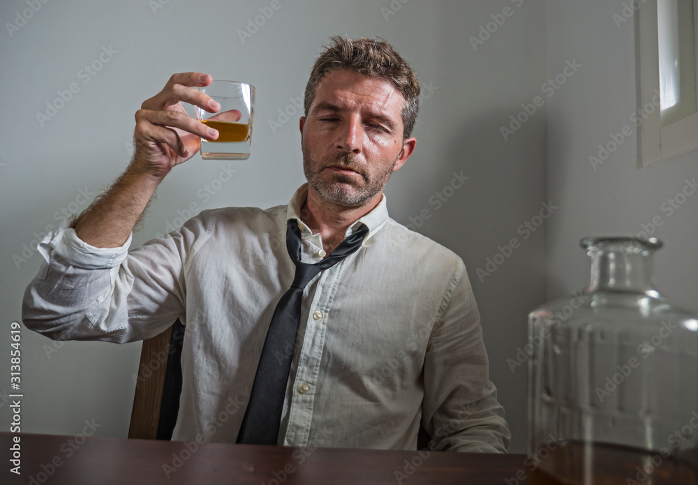 Fototapeta portrait of 30s to 40s alcoholic  man in lose necktie drinking desperate holding whiskey glass thoughtful drunk and depressed completely wasted in alcohol addiction concept