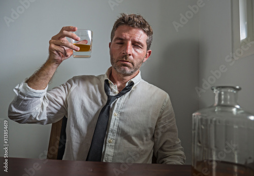 Obraz portrait of 30s to 40s alcoholic  man in lose necktie drinking desperate holding whiskey glass thoughtful drunk and depressed completely wasted in alcohol addiction concept - fototapety do salonu