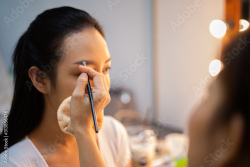 Cuadros en Lienzo hand of make up artist doing make up of asia young beautyful woman Actress in st