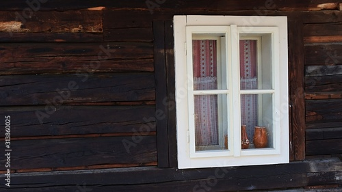 Antique wooden window with white painted window frame on the wall of historical blockhouse in northern Slovakia Canvas Print