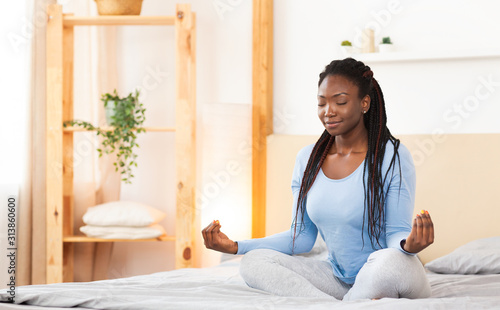 Black Girl Doing Morning Yoga In Bed At Home - 313860600