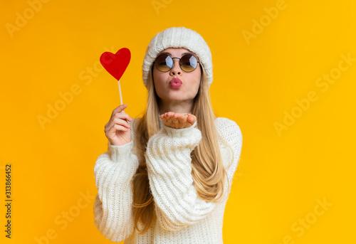 Obraz Lovely girl holding heart card and sending flying kiss - fototapety do salonu