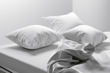 Unmade Bed With Soft Clean Whi...