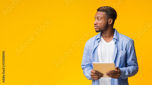 Fotografia  Afro Guy Holding Digital Tablet Looking Aside, Yellow Background, Panorama