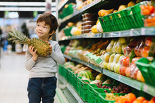 Pretty Boy With Pineapple In Supermarket