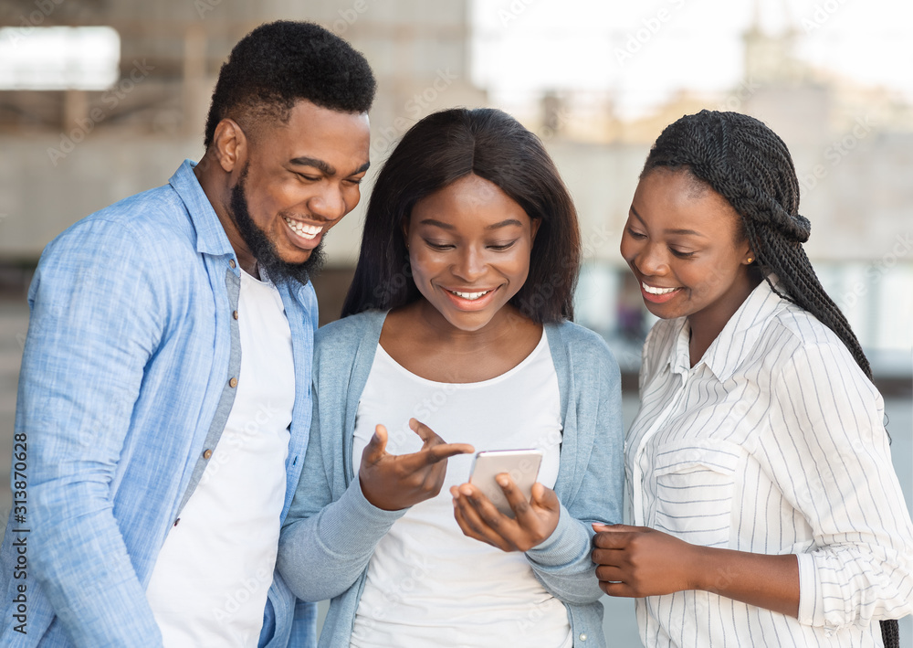 Fototapeta Millennial afro girl showing funny content on smartphone to friends
