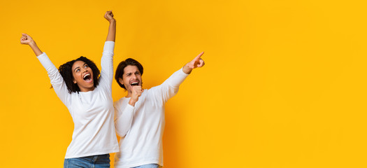 Multiracial couple dancing and singing together, having fun over yellow background