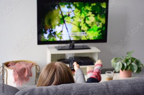 Young woman watching television with subtitles while sitting comfortably on sofa at home in living room Fototapet