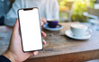 canvas print picture - Mockup image of a man holding black mobile phone with blank white screen with woman drinking coffee in cafe