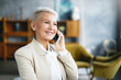 canvas print picture - Isolated portrait of confident mature businesswoman talking on cell phone, enjoying nice conversation, wearing stylish beige jacket. Blonde saleswoman calling to client, discussing details of order