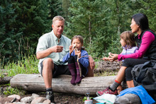 Family Whiddling Sticks To Roast Marshmallows While Backpacking In The Gore Range, Colorado