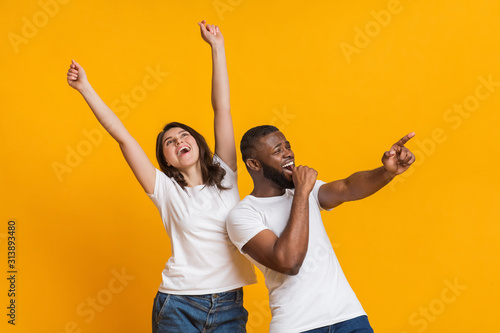 Joyful international couple having fun together, emotionally dancing and singing Wallpaper Mural