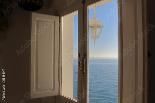Vistas al mar mediterráneo desde la ventana de una habitación en un día soleado y con la mar en calma