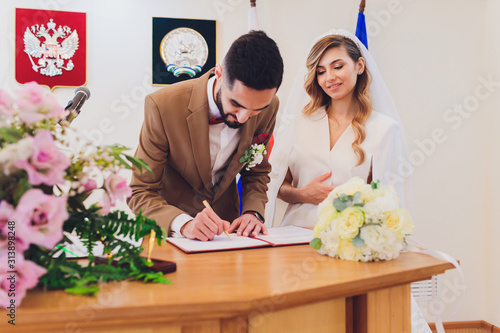 Photo newlyweds append signatures in a registry office during wedding registration