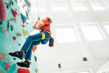 Teenager Boy At Indoor Climbing Wall Hall. Boy Is Climbing Using A Top Rope,chalk Bag And Climbing Harness. Active Teenager Time Spending Concept Image.